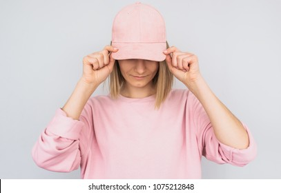 Closeup portrait of Caucasian blonde young female wearing pink sweater and cover her eyes with pink cap, protect from the sun rays, isolated on white studio background. Positive people emotion concept