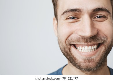 Close-up portrait of caucasian male model joyfully smiling with white perfect teeth. Good-looking happy carefree guy with stubble expressing positive emotions and feelings.
