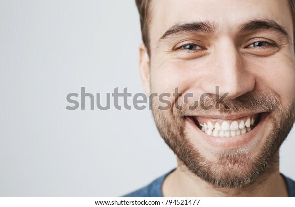 Nahaufnahme des Porträts eines kaukasischen männlichen Models fröhlich lächelnd mit weißen perfekten Zähnen. Guter, fröhlicher und sorgenfreier Kerl mit stubelnden Ausdrücken positiver Emotionen und Gefühle.