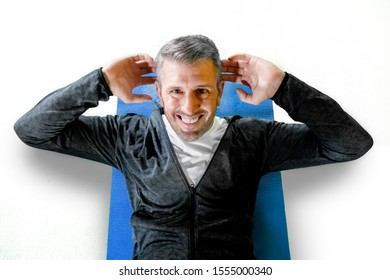 Closeup portrait of caucasian man doing sits up on a blue mattress, training isolated on white background