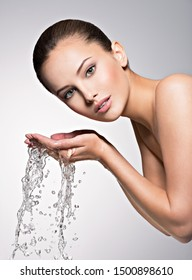 Closeup portrait of a caucasian woman washing her clean face with water