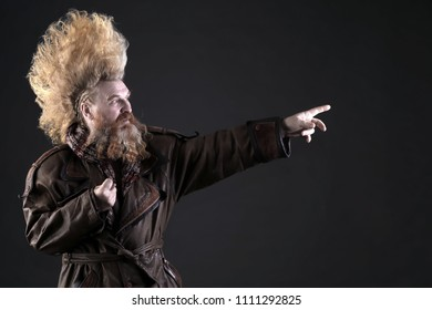 closeup portrait of a charismatic adult man with a beard and high mohawk in the studio on a dark background