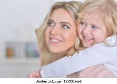 Close-up portrait of a charming little girl with mom at home