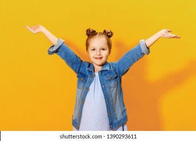 Closeup portrait of a charming little kid girl on a yellow background. The child raised his hands palm up.