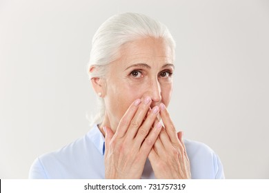 Close-up portrait of charming old lady, covering her mouth with hands, looking at camera, isolated over white background
