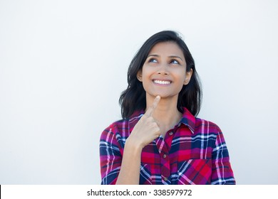 Closeup portrait, charming upbeat smiling joyful happy young woman looking upwards daydreaming something nice, isolated white wall background. Positive human emotions facial expressions feelings
