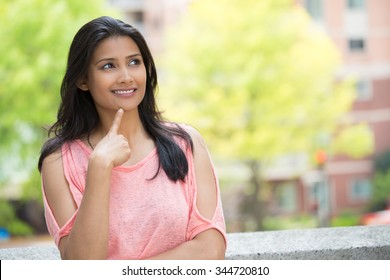 Closeup portrait, charming upbeat smiling joyful happy young woman looking upwards daydreaming something nice, isolated outdoors background. Positive human emotions facial expressions feelings