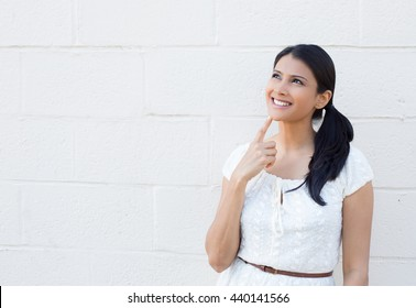 Closeup portrait, charming upbeat smiling joyful happy young woman looking upwards daydreaming something nice, isolated outdoors white background. Positive human facial expressions feelings