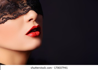 Close-up portrait of a charming  woman in black lace mask.