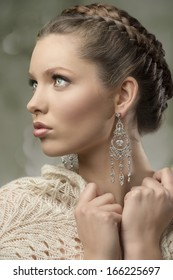 close-up portrait of charming woman with splendid eyes, elegant hair-style, precious earrings and wool shawl