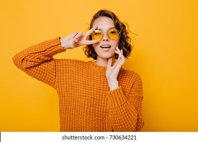Close-up portrait of charming young woman with gently smile posing with peace sign in trendy glasses. Stylish girl in bright sweater having fun during photoshoot in studio.
