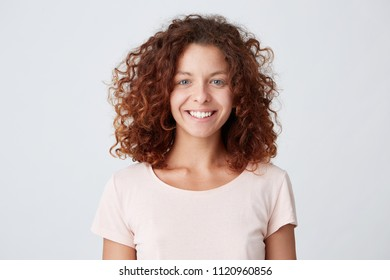 Closeup portrait of cheerful beautiful young woman with curly hair, wears casual t-shirt  looks directly into camera, isolated over white background