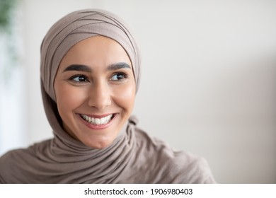 Closeup portrait of cheerful muslim lady in stylish headscarf looking at copy space, panorama. Happy arab woman in hijab watching advertisement and smiling. Job opportunities for arab women