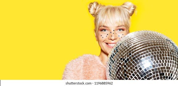 Close-up portrait of cheerful smiling girl wearing festive makeup and getting ready for party. Positivity and disco ball concept. Isolated on yellow background