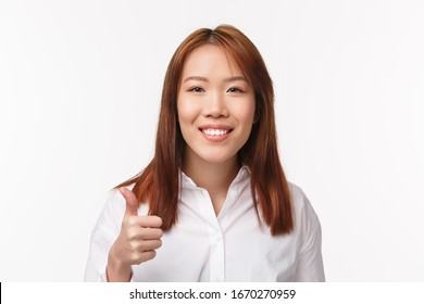 Close-up portrait cheerful smiling pleased asian woman in white shirt, say good job, nice work, make thumb-up gesture in approval or agree, nod acceptingly, standing white background