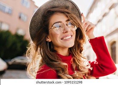 Close-up portrait of cheerful white woman in glasses touching her hat on blur background. Photo of fashionable girl with beautiful brown hair smiling to camera.