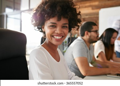 Closeup portrait of cheerful young african woman sitting in conference room with coworkers in background. Creative team meeting in boardroom.