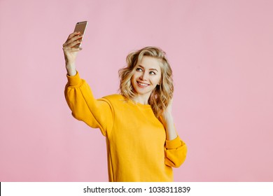 close-up portrait of cheerful  young caucasian female with curly blonde hair, in yellow sweater poses on a pink background. woman takes a selfie on the camera of the smartphone