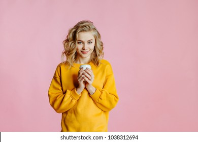 close-up portrait of cheerful  young caucasian female with curly blonde hair, in yellow sweater poses on a pink background. woman holds in hand a glass with coffee and smiles