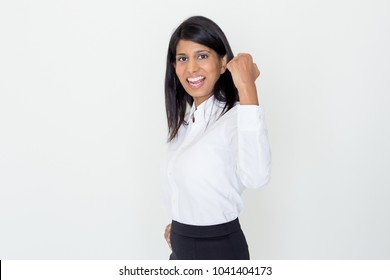 Closeup portrait of cheerful young pretty Indian business woman looking at camera and pumping fist. Business success concept. Isolated view on grey background.