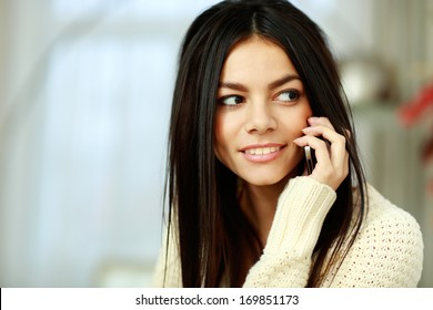 Closeup portrait of a cheerful young woman talking on phone