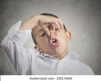 Closeup portrait child boy with disgust on face pinches his nose something stinks bad smell situation isolated grey wall background. Negative human emotions facial expressions perception body language