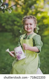 Close-up portrait of a child with a watering can in the garden.