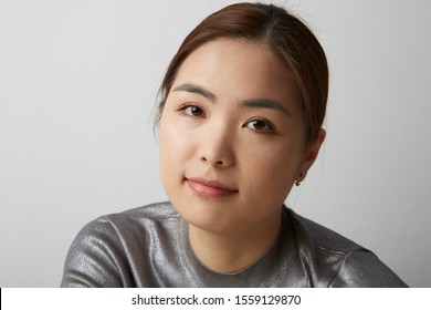 Close-up portrait of Chinese woman posing on the white background with her hands crossed. Isolated.