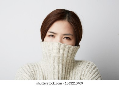 Close-up portrait of Chinese woman posing on the white background. Isolated.