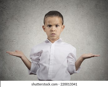 Closeup portrait clueless, unhappy child boy with arms out asking what's problem who cares, so what, I don't know isolated grey wall background. Negative human emotion facial expression body language