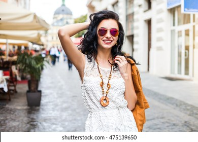Close-up portrait of a confident free amazing lady, she walks through the city, dressed in a white dress, a brown jacket, stylish accessories, bohemia, boho style, long dark hair, makeup, urban style