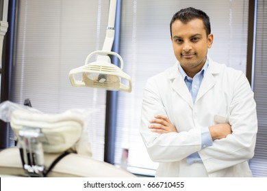 Closeup portrait of confident healthcare professional with arms folded standing next to white patient chair