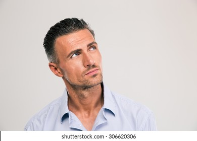 Closeup portrait of a confident man looking away at copyspace over gray background