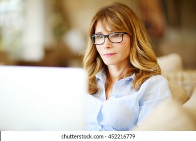 Close-up portrait of confident middle aged businesswoman using her laptop while working at home.