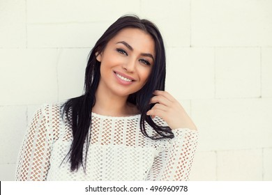 Closeup portrait of confident smiling happy pretty young woman in white shirt, isolated background white wall background. Positive human emotion facial expression feelings, attitude, perception