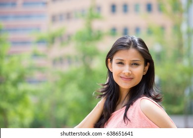 Closeup portrait of confident smiling happy pretty young woman in pink dress, isolated background of blurred trees, buildings. Positive human emotion facial expression feelings, attitude, perception