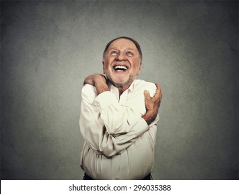 Closeup portrait confident smiling man holding hugging himself isolated on grey wall background. Positive human emotion, facial expression, feeling, reaction, attitude. Love yourself concept
