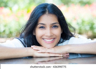 Closeup portrait confident smiling pretty young woman resting face on hands in white shirt, isolated background blurred flowers. Positive human emotion facial expression feelings, attitude