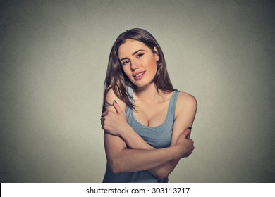 Closeup portrait confident smiling woman holding hugging herself isolated gray wall background. Positive human emotion, facial expression, feeling, reaction, situation, attitude. Love yourself concept