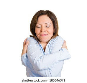 Closeup portrait, confident woman holding hugging herself, isolated white background. Positive emotion facial expression feeling, reaction, situation, attitude. Love yourself concept