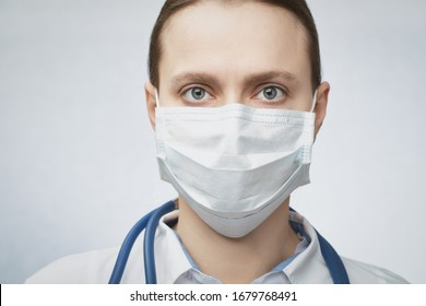 Close-up portrait of confident young female doctor wearing protective surgical mask