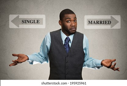 Closeup portrait confused looking clueless business man arms out asking which way to go in life isolated black background with single, married arrows. Emotion facial expression feeling life perception
