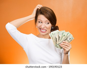 Closeup portrait, confused stressed woman holding cash dollars in hand, scratching head wondering how to spend. More money, more problems concept. Negative human emotions, facial expressions, feelings