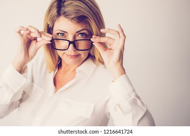 Closeup portrait of content middle-aged attractive fair-haired woman looking at camera over her glasses. Female teacher concept. Isolated front view on grey background.