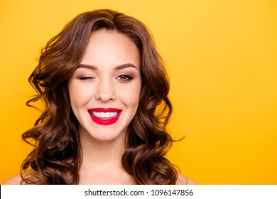 Closeup portrait with copy space empty place of pretty trendy girl with beaming smile red pomade modern hairdo winking with one eye isolated on yellow background