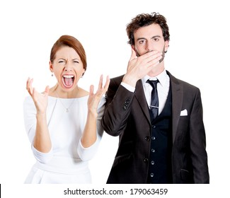 Closeup portrait couple, man, woman, corporate workers, one being noisy, screaming, yelling, other quiet, calm, thoughtful, modest, covering closed mouth isolated on white background. Emotion contrast
