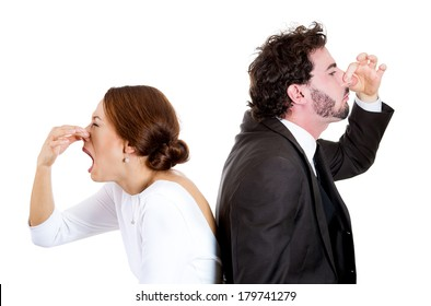 Closeup portrait of couple man woman standing back to back pinching noses, dislike, disgusted by each other, isolated on white background. Negative human face expressions, emotions, reaction, attitude
