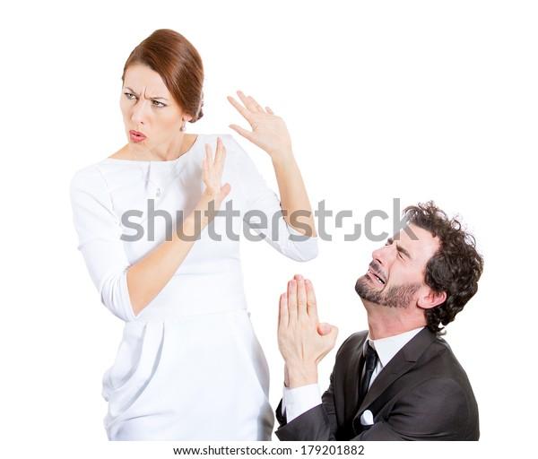 夫婦、男性、女性の接写。白い背景に悲しい夫がひざまずき、謝罪を受け入れるのを嫌がる許しの妻を求める。人間の感情、顔の表情