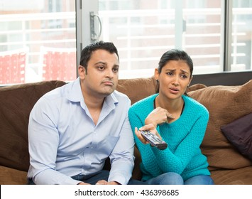 Closeup portrait, couple sitting on brown leather couch, watching TV, holding remote, sad by what they see, isolated indoors flat background.