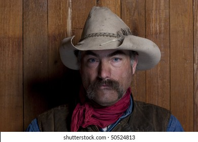 Close-up portrait of a cowboy with a mustache in front of a rough wood wall. He is staring at the camera with a serious expression. Horizontal format.
